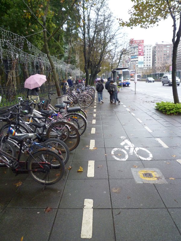 鬧巿街道旁的單車泊位及清楚標示出的單車通道,留意是和行人道並行而無需分隔。